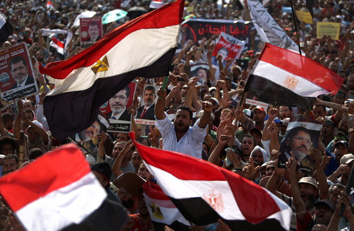 Egyptian supporters of deposed president Mohamed Morsi (portrait) wave their national flag as they attend a rally in support of the former Islamist leader outside Cairo's Rabaa al-Adawiya mosque on July 8, 2013 (AFP Photo / Mahmud Hams)