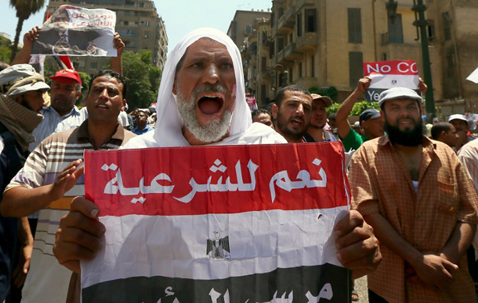 "A supporter of the Muslim Brotherhood and Egypt's ousted president Mohamed Morsi, holds up a paper Egyptian flag with the words in Arabic, ""Yes to Legitimacy"" as they demonstrate along a road leading to the government headquarter on July 17, 2013. (AFP Photo / Marwan Naamani)"