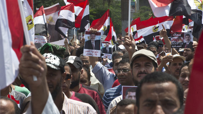 Supporters of the Muslim Brotherhood and ousted Egyptian president Mohamed Morsi wave Egyptian flags while holding pictures of Morsi as they march towards Cairo University to demand his reinstatement in Cairo on July 19, 2013.(AFP Photo / Khaled Desouki)
