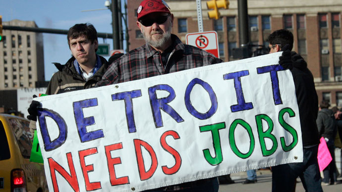 "Chrysler Transport worker James Theisen carries a ""Detroit Needs Jobs"" sign as he joins a demonstration of about a dozen workers demanding jobs, in front of Cobo Center in Detroit.(Reuters / Rebecca Cook)"