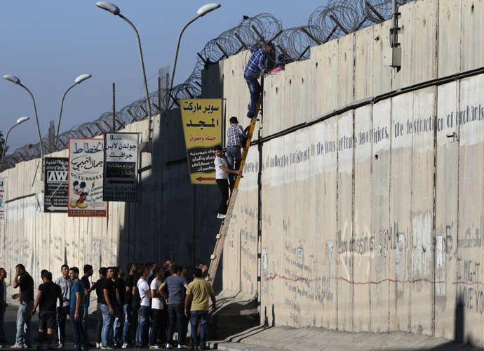Palestinian men climb a section of Israel's separation barrier as they try to avoid crossing Israeli-controlled checkpoints to reach the al-Aqsa mosque compound in Jerusalem's Old City, on July 26, 2013, on the third Friday of the holy month of Ramadan (AFP Photo / Abbas Momani)