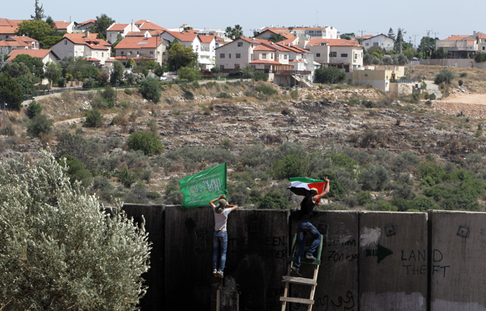 Palestinian protester climbs Israel's controversial separation barrier during clashes with Israeli security forces following a demonstration against Israeli settlements and its separation wall, in the West Bank village of Nilin near the Jewish settlement of Hashmonaim (background), on June, 7, 2013 (AFP Photo / Abbas Momani)