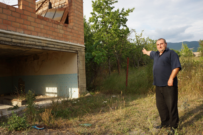 Levan shows the border fence made from his own vines. In this place, the demarcation line passes through his house (RT Photo / Nadezhda Kevorkova)