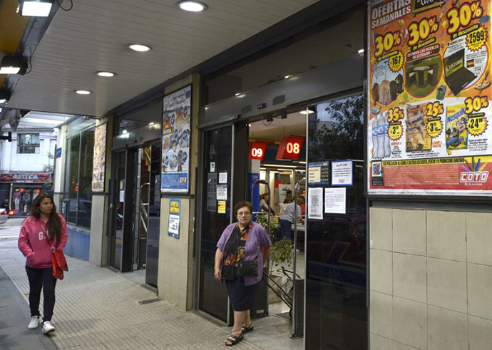 A woman leaves a supermarket with a promotional poster outside in Buenos Aires (AFP Photo / Juan Mabromata)