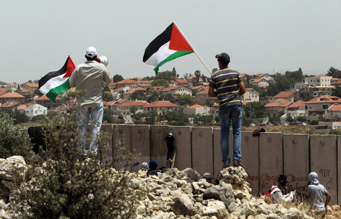 Palestinian protesters wave the national flag as their comrades climb Israel's controversial separation barrier. (AFP Photo / Abbas Momani)