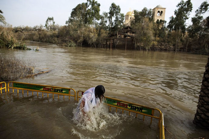 Christian Orthodox pilgrim immerses herself into the waters of the Jordan River during a baptism ceremony marking the Orthodox Feast of the Epiphany on January 18, 2013 at the Qasr al-Yahud baptismal site in the West Bank by the Jordan River. (AFP Photo / Menahem Kahana)