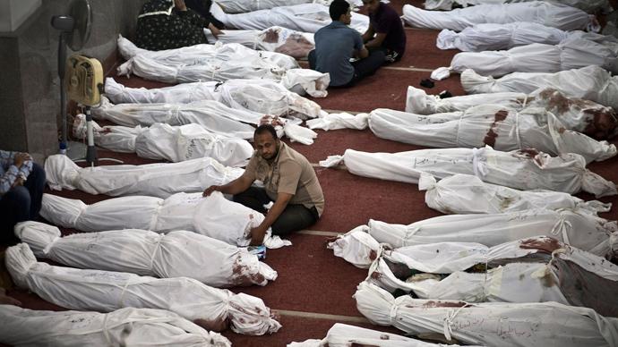 Egípcios choram sobre os corpos envoltos em mortalhas em uma mesquita no Cairo 15 de agosto de 2013 (Foto: AFP / Khaled Mahmoud)