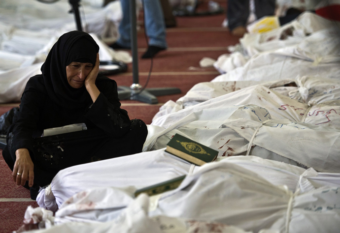An Egyptian woman mourns over the body of her daughter wrapped in shrouds at a mosque in Cairo on August 15, 2013 (AFP Photo / Khaled Desouki)