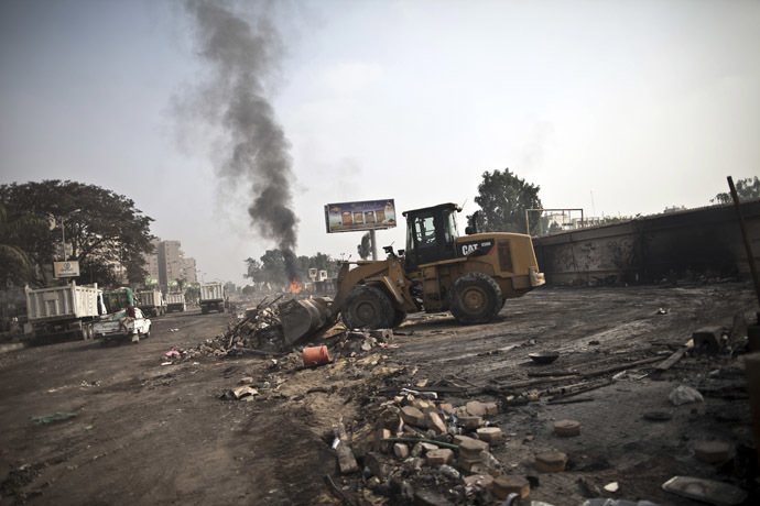 A tractor clears the debris at Rabaa al-Adawiya square in Cairo on August 15, 2013, as smoke billows in the background, following a crackdown on the protest camps of supporters of Egypt's ousted Islamist leader Mohamed Morsi the previous day. (AFP Photo)