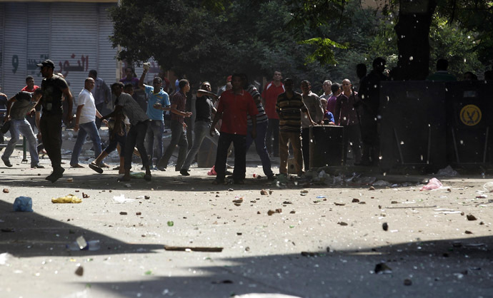 Police men and residents throw stones in front of Azbkya police station during clashes with protesters who support ousted Egyptian President Mohamed Mursi at Ramses Square in Cairo, August 16, 2013. (Reuters/Amr Abdallah Dalsh)