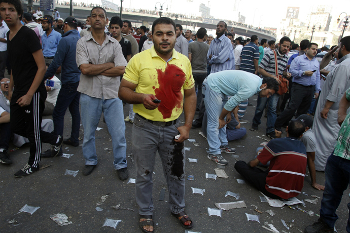 A supporter of the Muslim Brotherhood and Egypt's ousted president Mohamed Morsi stands in a blood-stained clothes as demonstrators gather in Cairo's Abbassiya neighbourhood on August 16, 2013 (AFP Photo / Mohammed Abdel Moneim)
