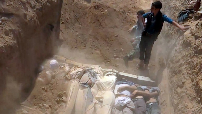 An image grab taken from a video uploaded on YouTube by the Local Committee of Arbeen on August 21, 2013 allegedly shows Syrians covering a mass grave containing bodies of victims that Syrian rebels claim were killed in a toxic gas attack by pro-government forces in eastern Ghouta and Zamalka, on the outskirts of Damascus. (AFP Photo)
