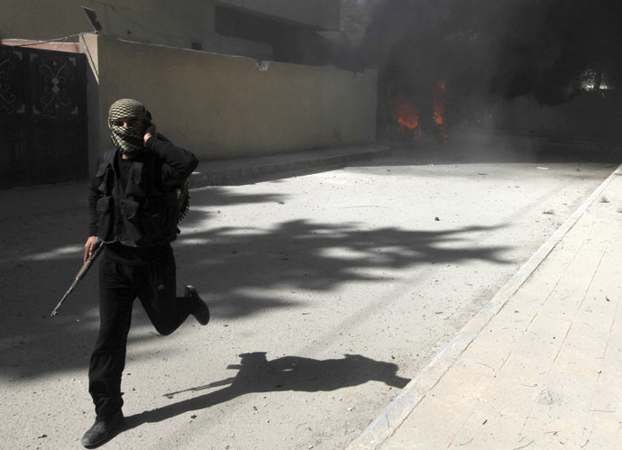 A fighter from Islamist Syrian rebel group Jabhat al-Nusra runs with his weapon as their base is shelled in Raqqa province, eastern Syria, March 14, 2013. (Reuters/Hamid Khatib)