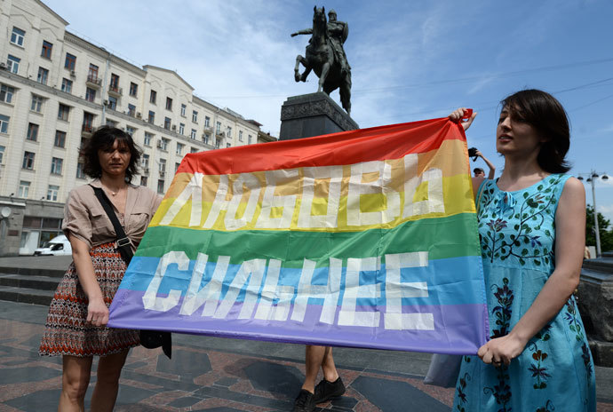 "Participants in an unauthorized rally held by gay activists next to the Yury Dolgoruky monument on Tverskaya Square in Moscow. The sign reads ""Love is Stronger"" (RIA Novosti / Alexey Filippov)"