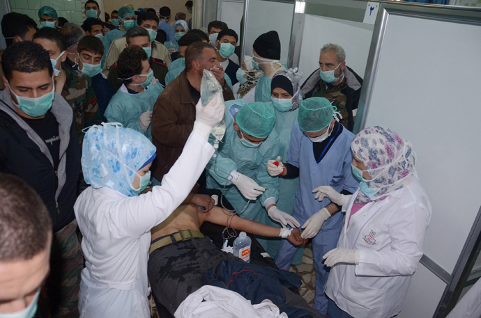 In this image made available by the Syrian News Agency (SANA) on March 19, 2013, medics and other masked people attend to a man at a hospital in Khan al-Assal in the northern Aleppo province, as Syria's government accused rebel forces of using chemical weapons for the first time (AFP Photo)