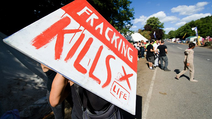 """A climate and anti-fracking protester holds a """"Fracking kills"""" placard as he stands outside the test drill site operated by British energy firm Cuadrilla Resources in Balcombe, southern England, on August 20, 2013. (AFP Photo / Leon Neal)"""