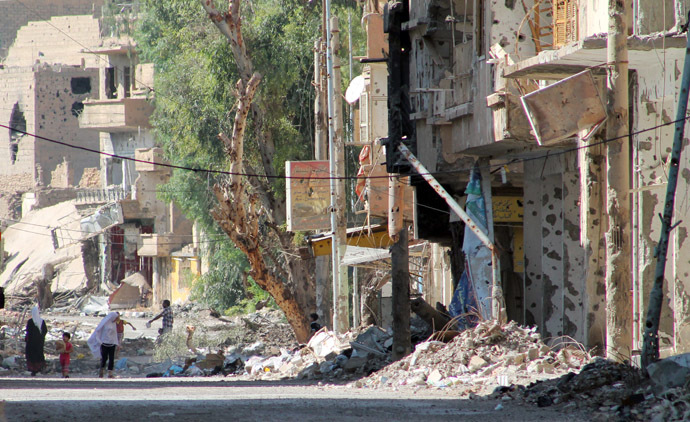 Syrians walk in a heavily damaged street in Syria's eastern town of Deir Ezzor on August 26, 2013. (AFP Photo)