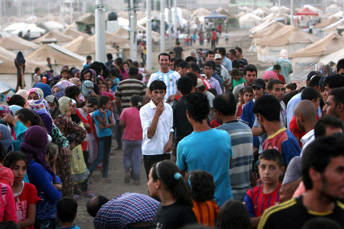 Syrian-Kurdish refugee families queue to get food at the Quru Gusik refugee camp, 20 kilometres east of Arbil, the capital of the autonomous Kurdish region of northern Iraq, on August 27, 2013. (AFP Photo/Safin) Hamed
