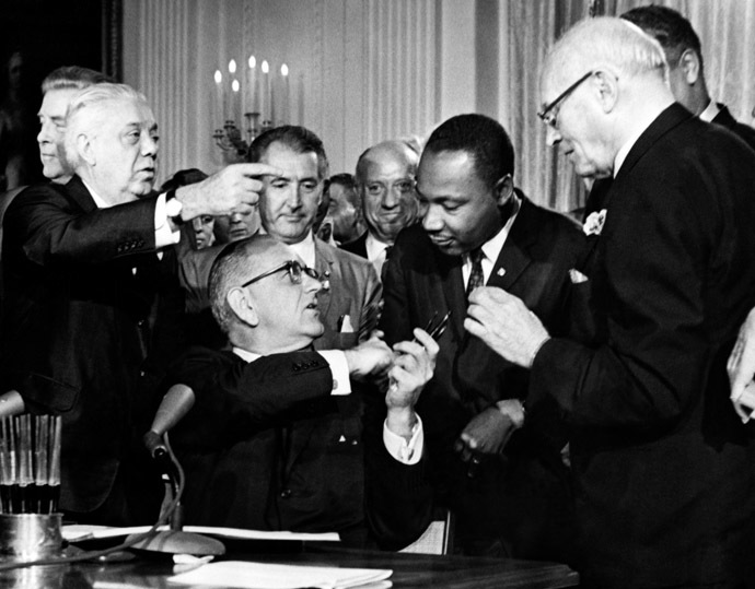 US President Lyndon B. Johnson hands a pent to the Rev. Martin Luther King (2nd-R) after signing the historic Civil Rights Bill in the East Room of the White House, in Washington, D.C., 02 July 1964. (AFP Photo)