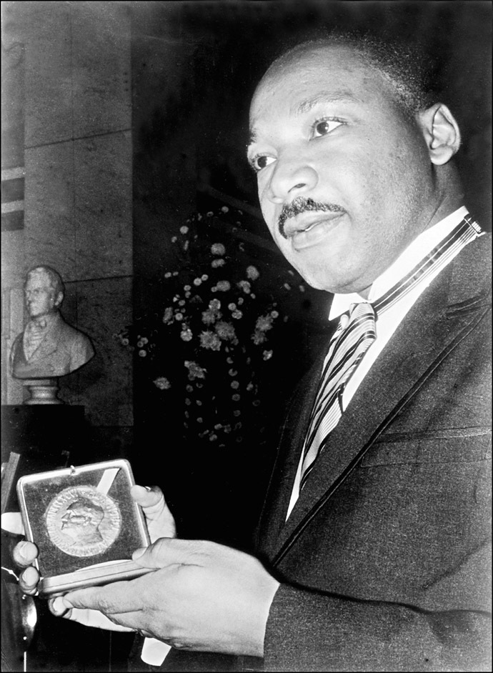 US clergyman and leader of the Movement against Racial Segregation Martin Luther King, displays 10 December 1964 in Oslo his Nobel Peace Prize medal. (AFP Photo)