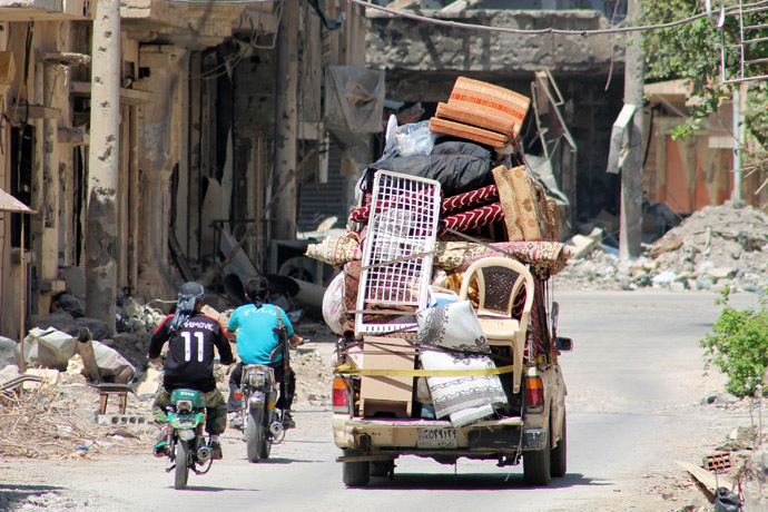 yrian young men drive their motorbikes past a pick up truck loaded notably with matresses, chairs and carpets in a street of the old airport neighbourhood of the Syria's eastern town of Deir Ezzor on August 27, 2013. (AFP Photo)