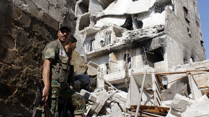 Free Syrian Army fighters stand in front of buildings damaged by what activists said was shelling by forces loyal to Syria's President Bashar al-Assad in the old city of Aleppo September 2, 2013. (Reuters/Molhem Barakat)