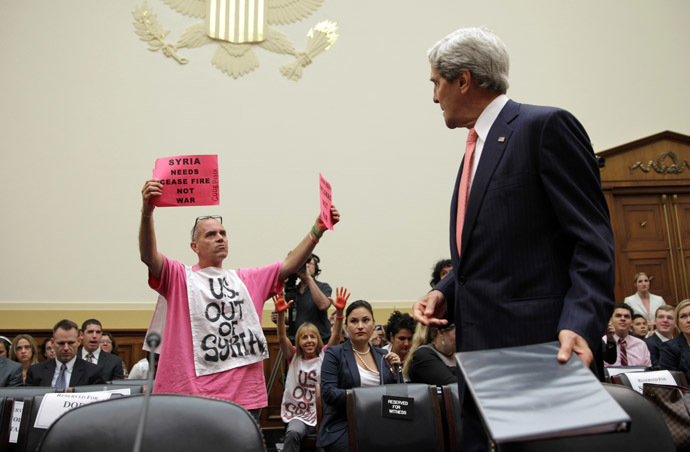 "Members of CodePink, Tighe Barry (L) and Medea Benjamin (2nd L) protest as U.S. Secretary of State John Kerry (R) arrives at a hearing on ""Syria: Weighing the Obama Administration's Response"" before the House Foreign Affairs Committee September 4, 2013 on Capitol Hill in Washington, DC. (Alex Wong/Getty Images/AFP )"