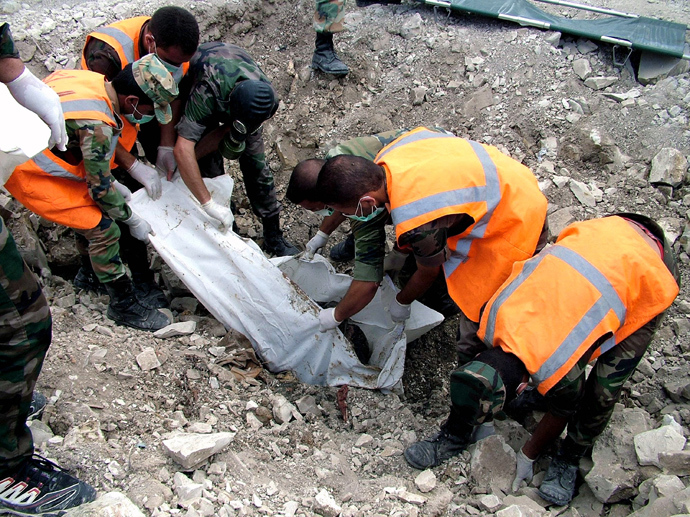 A handout picture released by the Syrian Arab News Agency (SANA) on August 20, 2013 shows soldiers loyal to the regime forces wrapping a decomposed body that was allegedly discovered in a mass grave in northern Latakia, a province on the Mediterranean coast (AFP Photo)