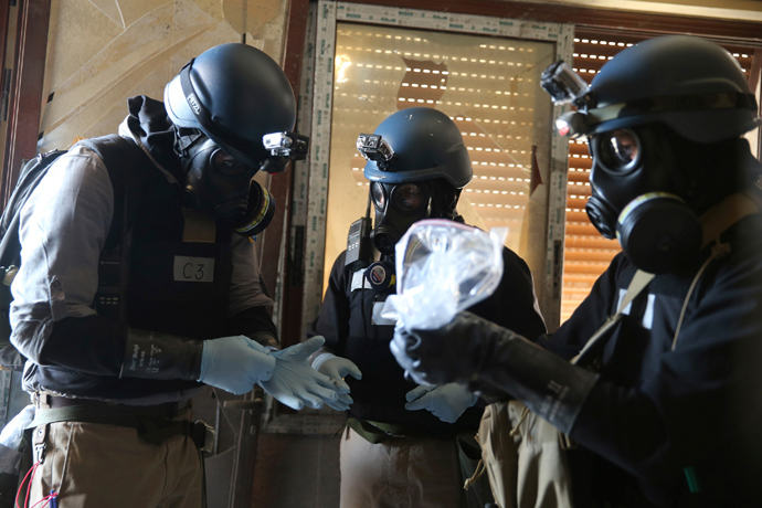 A U.N. chemical weapons expert, wearing a gas mask, holds a plastic bag containing samples from one of the sites of an alleged chemical weapons attack in the Ain Tarma neighbourhood of Damascus August 29, 2013 (Reuters / Mohamed Abdullah)