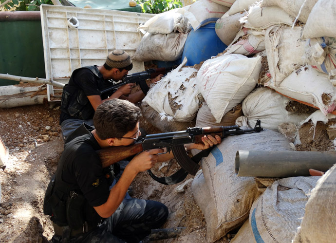 Free Syrian Army fighters take up positions behind piled sandbags as they aim their weapons in the eastern al-Ghouta, near Damascus September 8, 2013. Picture taken September 8, 2013. (Reuters/Msallam Abd Albaset)