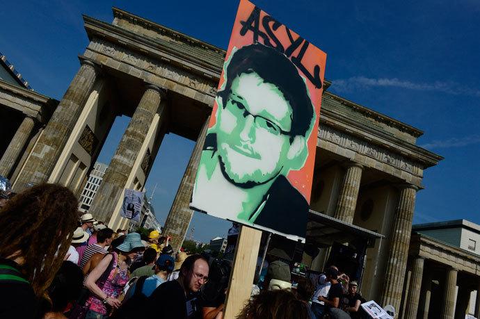 Demonstrators hold up a placard in support of former US agent of the National Security Agency, Edward Snowden in front of Berlin's landmark Brandenburg Gate as they take part in a protest against the US National Security Agency (NSA) collecting German emails, online chats and phone calls and sharing some of it with the country's intelligence services in Berlin on July 27, 2013.(AFP Photo / John Macdougall)
