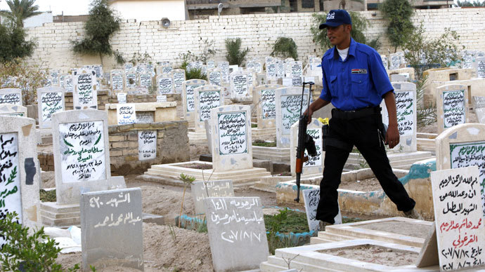 "An Iraqi security officer walks past headstones in the ""Martyr's Cemetery"" in the city of Fallujah.(AFP Photo / Ali Al-Saadi)"