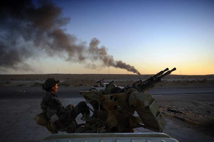 A rebel fighter looks on as he sits on an anti-aircraft machine gun on August 29, 2011 near Ras Lanuf while smoke pours from a rafinery. (AFP Photo)