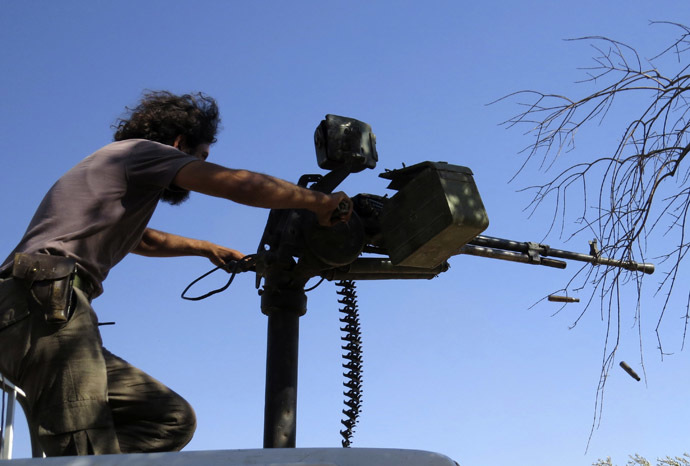 A Free Syrian Army fighter fires his weapon during what the FSA said were clashes with forces loyal to Syria's President Bashar al-Assad in Idlib, September 9, 2013. Picture taken September 9, 2013. (Reuters/Muhammad Qadour)