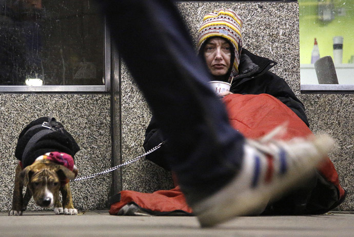 A homeless woman from north Wales, sits huddled under a sleeping bag next to her dog in a shopping arcade near the Victoria rail station in central London (Reuters/Chris Helgren)