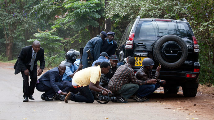 Police officers and members of the media take cover at a distance from the Westgate Shopping Centre after continuous gunfire was heard coming from the mall in Nairobi September 23, 2013.(Reuters / Siegfried Modola)