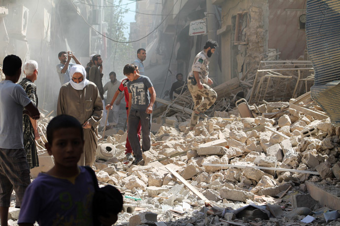 Residents of Syria's eastern town of Deir Ezzor walk past the debris of a building reportedly hit by a missile on September 26, 2013. (AFP Photo/Ahmad Aboud)