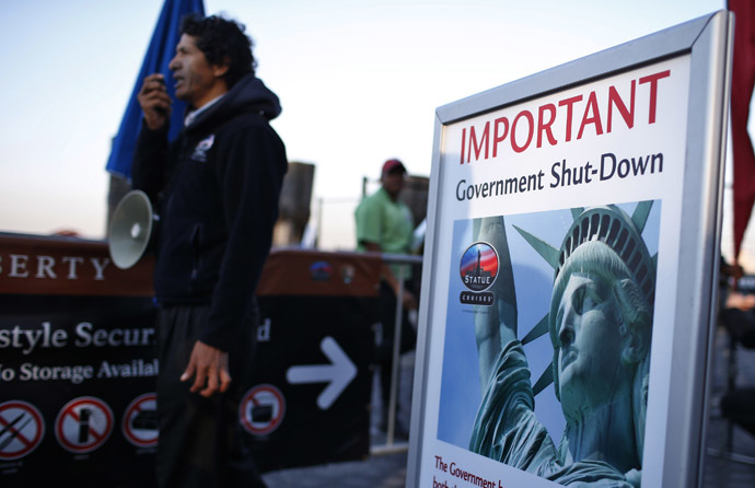 A man with a megaphone announces the closure of the Statue of Liberty, a U.S. National Park, due to the U.S. Government shutdown to tourists at the ferry dock to the Statue of Liberty in Battery Park in New York, October 1, 2013. (Reuters/Mike Segar)