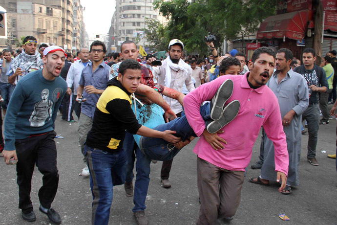 Egyptian Muslim brotherhood and supporters of ousted president Mohamed Morsi carry an injured comrade during clashes with riot police along Ramsis street in downtown Cairo on October 6, 2013. (AFP Photo)