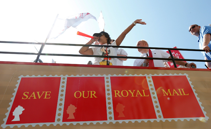 Postal workers travel aboard an open top bus as they campaign against the privatisation of the Royal Mail, London (Reuters / Suzanne Plunkett)