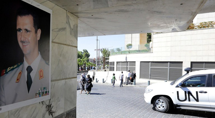 (FILES) A photo taken on October 9, 2013 shows a poster of Syrian President Bashar al-Assad on a wall as a United Nations vehicle carrying inspectors from the Organisation for the Prohibition of Chemical Weapons (OPCW) leaving a hotel in Damascus (AFP Photo / Louai Beshara)