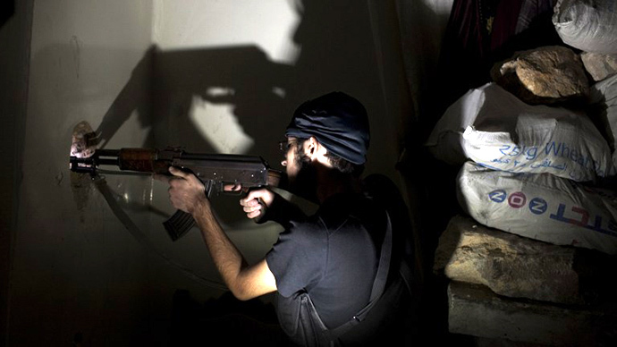 Opposition fighter Abu Yassin, 21, takes position inside a building in Salaheddin square, in Syria's northern city of Aleppo, on September 30, 2013. (AFP Photo / Jm Lopez)
