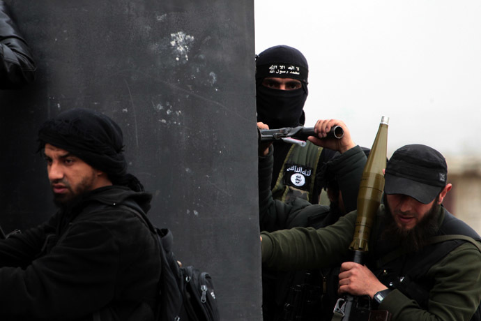 A Turkish fighter of the jihadist group Al-Nusra Front, bearing the flag of Al-Qaeda on his jacket (C-back), holds position with fellow comrades on April 4, 2013 in the Syrian village of Aziza, on the southern outskirts of Aleppo. (AFP Photo)