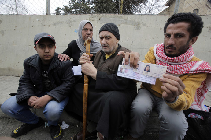 Palestinians who fled violence in the Syrian refugee camp of Yarmuk are seen at the Masnaa Lebanese border crossing with Syria as people stamp their documents before entering Lebanon (AFP Photo)