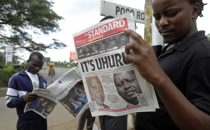 Nairobi resident read on March 31, 2013 in Nairobi the newspaper with the headline of Kenyan fourth president Uhuru Kenyatta's win, following the supreme court's decision that he was duly elected. (AFP Photo/Simon Maina)