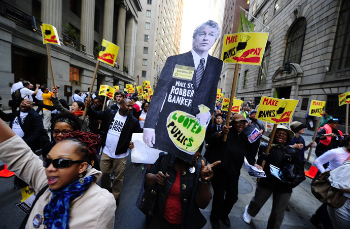 Labor-Community Coalition activists march down Wall Street holding a cutout of JP Morgan CEO Jamie Dimon, during a protest against budget cuts and bank practices, in New York, May 12, 2011. (AFP Photo / Emmanuel Dunand)