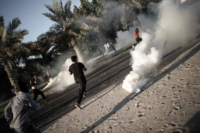 Bahraini protesters run away from tear gas and bird shot fired by riot police during clashes following the funeral of Ali Khalil Sabbagh in the village of Bani Jamrah, west of Manama, on October 23, 2013 (AFP Photo / Mohammed Al-Shaikh)