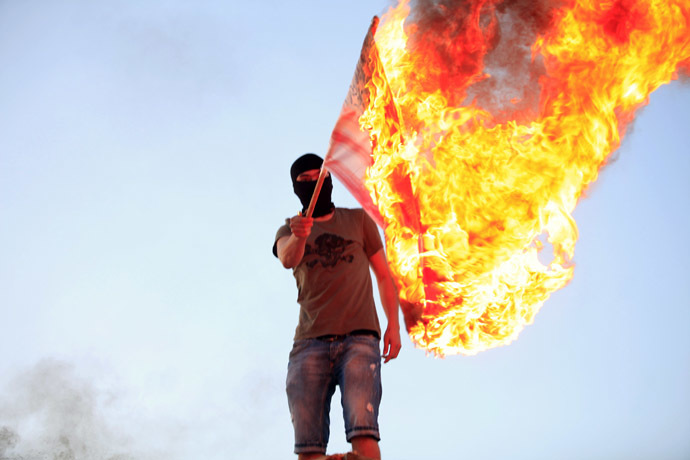 A protester burns a U.S. flag during a demonstration over the capture of senior al Qaeda figure Abu Anas al-Liby by U.S. authorities, in Benghazi October 11, 2013. (Reuters/Esam Omran Al-Fetori)