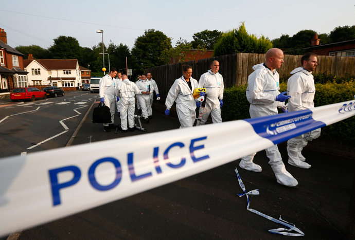 Police forensic officers walk behind a police cordon after an expolosion in Tipton, central England, July 12, 2013 (Reuters / Darren Staples)