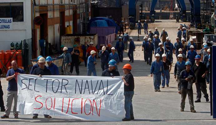 """Zamakona shipyard workers hold a banner reading """"Shipyard solution"""" as they take part in a protest against the repayment of state aids by Spanish shipbuilders in the Northern Spanish Basque village of Pasajes de San Pedro (AFP Photo / Rafa Rivas)"""